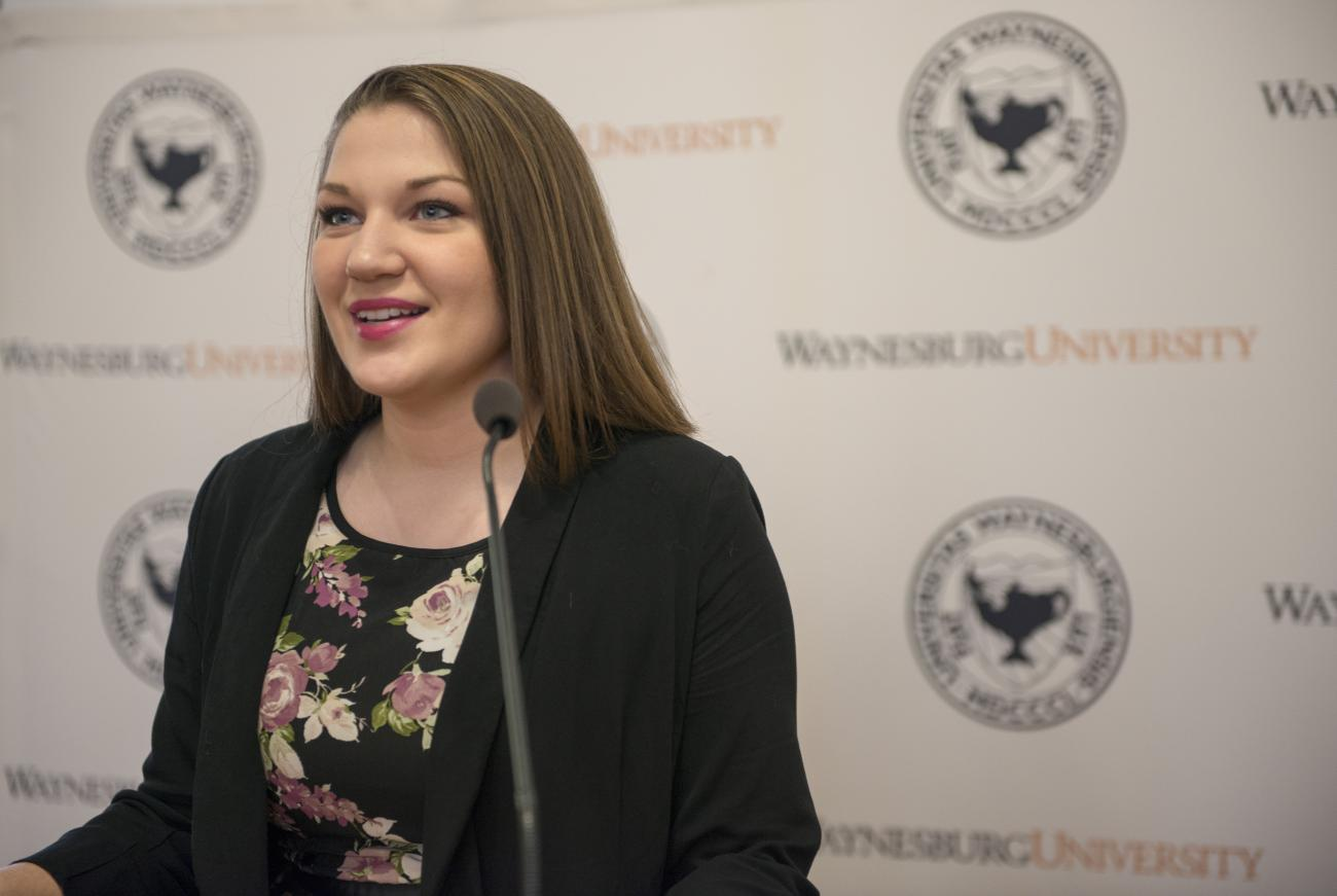 Public Relations student, Maura, announces WU's President at a press conference