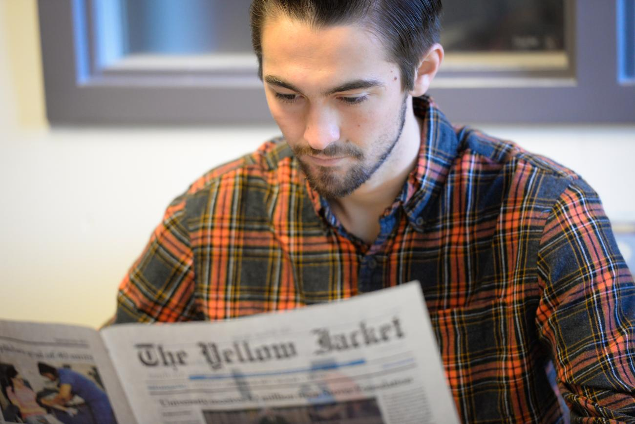 Student reads the university news paper.